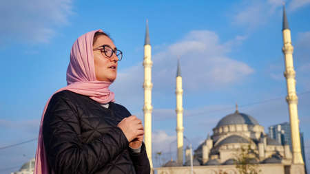 Young woman in a pink scarf and glasses whispers something while holding her hands on the background of the mosque. 스톡 콘텐츠
