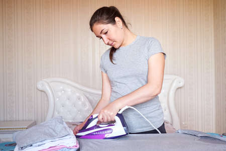 Young smiling woman ironing things with iron. 스톡 콘텐츠