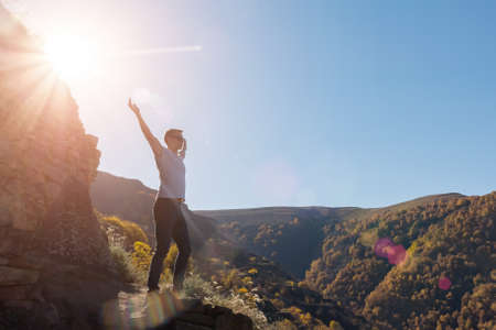 Muscular guy silhouette stands on rocky cliff edge at large stone against green forestry mountains at back bright sunlight on autumn day