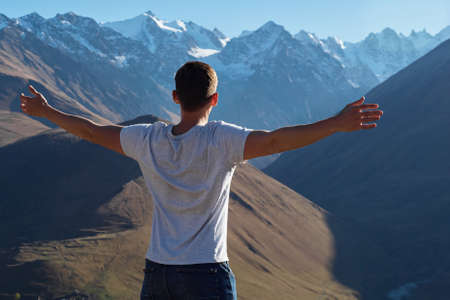 Athletic guy in white t-shirt stands on hilltop and looks at large mountains peaks stretching arms under bright sunlight backside view 스톡 콘텐츠