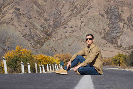 Man in brown shirt and sunglasses sits on empty grey asphalt road surrounded by yellow orange trees against large rocky mountain on autumn day
