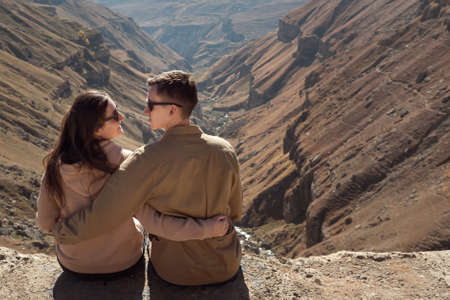 Romantic couple in love hugs and looks into eyes wearing sunglasses and sitting on steep cliff edge against mountain landscape side view