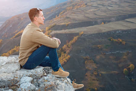 Young man sitting on a rock against the background of autumn trees, copyspace
