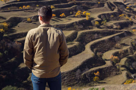 Guy in shirt and jeans looks at large terraced hills with brown fields and orange yellow trees under bright sunlight on autumn day backside view
