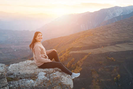 Young woman on a background of yellow trees sits on a protruding rock, sunlight.