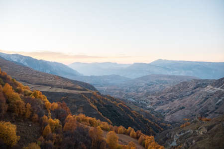 Wonderful large valley with ancient mountains covered with autumn forest and green fields under clear sky in evening panoramic view 스톡 콘텐츠