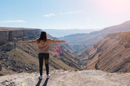 Young brunette woman in loose pink hoodie with hands up stands on cliff edge and enjoys picturesque mountain canyon with river on sunny day 스톡 콘텐츠