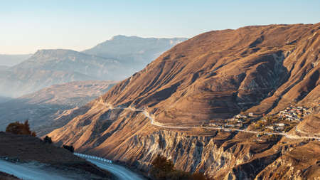 Empty contemporary highway runs along brown rocky slopes of high ancient mountain against clear blue sky on sunny autumn day aerial panorama