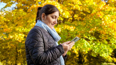 Young woman with phone on background of yellow trees. Zdjęcie Seryjne