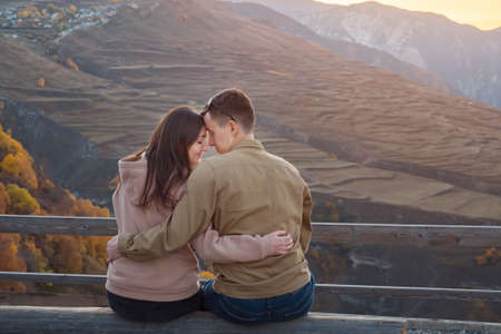 Young man and brunette girlfriend sits on bench on viewing point against picturesque ancient mountains at sunset Zdjęcie Seryjne