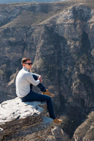 man in a gray turtleneck and sunglasses sits on a protruding rock. Zdjęcie Seryjne