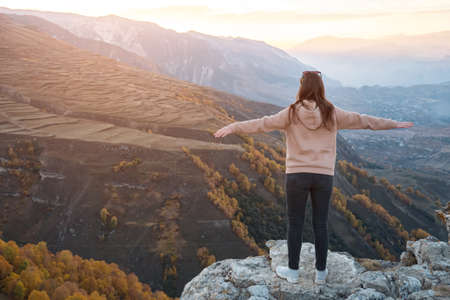 Young woman with loose flowing hair stands on grey rocky hilltop looking at bright sun rising from behind forestry hills backside view