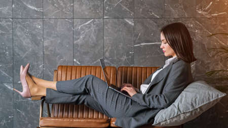 Young woman freelancer sits on brown bench with grey cushion and types on new laptop near green pot plant against marble wall at office reception