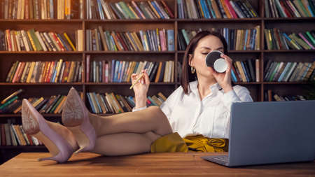 Sexy businesswoman in white blouse and yellow skirt twirls pencil drinks coffee and types on laptop putting legs on table in office against bookshelves