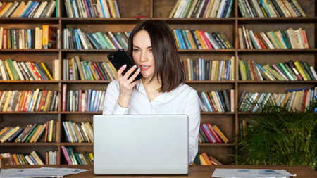 Happy brunette woman in stylish white blouse talks on mobile phone near contemporary laptop at table against large bookshelves in room Zdjęcie Seryjne