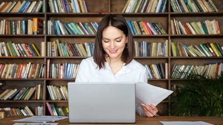 Smiling young woman in stylish white blouse works with papers near contemporary laptop at table against large library racks full of book