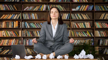 Short haired businesswoman meditates sitting in yoga pose on wooden table among rumpled paper sheets and laptop against bookshelves close-up Zdjęcie Seryjne