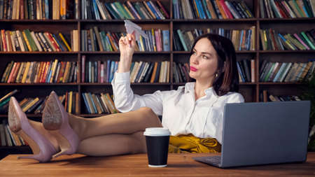 Joyful secretary in white blouse and yellow skirt plays with paper plane putting legs on table with grey laptop and coffee cup in office
