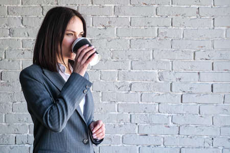 Smiling company manager in white blouse and grey classic costume drinks coffee from paper cup standing against brick wall before work copyspace