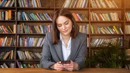 Stylish businesswoman in grey jacket over white blouse types on black smartphone and smiles sitting against book racks in library hall, sunlight Zdjęcie Seryjne