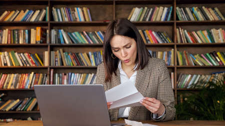 Young woman with short dark hair opens bank letter and touches cheek with shock sitting at laptop against wooden bookshelves at home Zdjęcie Seryjne