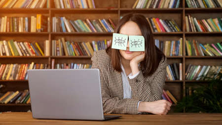 Brunette with short hair takes nap, holding head on hand with eye painting stickers on face near laptop on brown wooden table in office with books