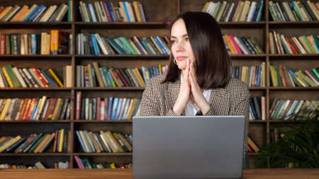 Businesswoman with short dark hair holds head on hands sitting at grey computer against large wooden racks with books in business office copyspace Zdjęcie Seryjne