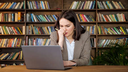 Thoughtful female project manager holds pen looking at laptop display and types sitting at brown table against wooden bookshelves in office Zdjęcie Seryjne