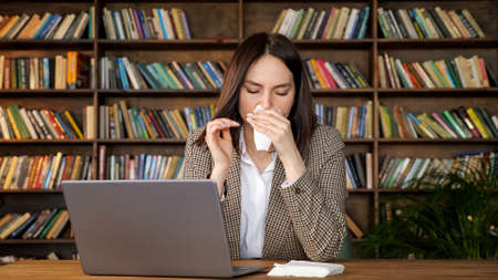 Young woman with short loose hair sneezes and takes white paper napkin sitting at grey laptop against coloured bookshelves in office