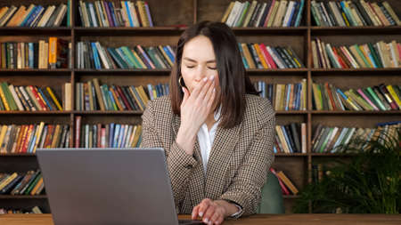 Tired businesswoman in brown jacket types on grey laptop and yawns sitting on chair at table against wooden racks with books at home