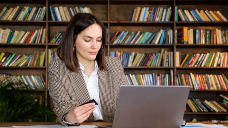 Online shopper in brown jacket enters credit card number typing on grey laptop sitting at table against large racks with books at home