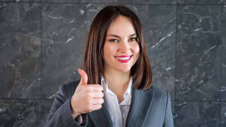 Young woman with short dark hair and red lipstick smiles and shows thumb-up posing against grey marble wall in new office close view