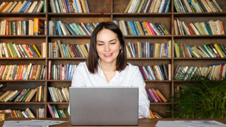 Positive lady in stylish white blouse takes part in online conference via contemporary laptop at table against racks full of books in office