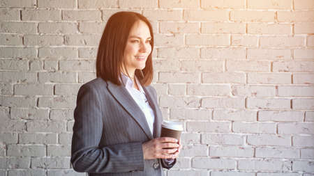 Smiling company manager in white blouse and grey classic costume drinks coffee from paper cup standing against brick wall before work closeup, sunlight