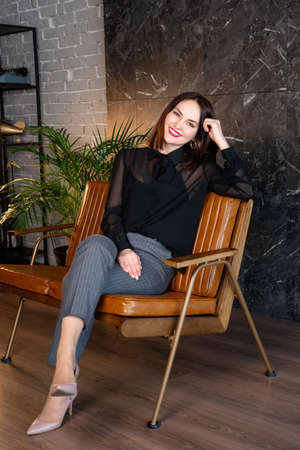 brunette woman sits on a leather armchair in formal clothes, a variant of an office wardrobe.