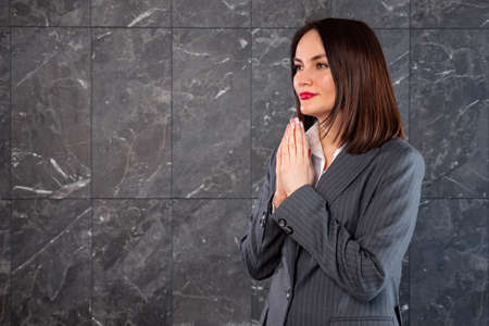 Beautiful woman in business gray suit looking with supplication at copy space. Zdjęcie Seryjne