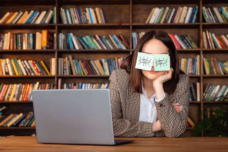 Funny lazy office worker napping at workplace covering eyes with sticky notes. Cheating to sleep concept Zdjęcie Seryjne