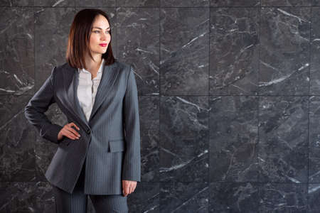 Young brunette in business gray suit, copyspace.