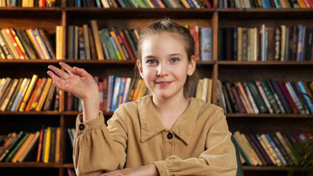 Schoolgirl in brown jacket waves hand talks and smiles to camera sitting at online lesson at home against coloured books on shelves closeup