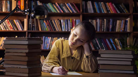 Tired girl writes home assignment on sheet of paper with pencil and yawns sitting among book stacks under electric lamp light in evening