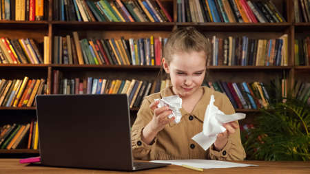 Serious girl in brown jacket writes essay and tears sheet of paper after mistake with anger sitting by black laptop at home with large bookshelves