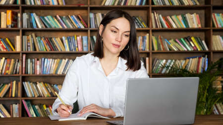 Attractive young lady in stylish white blouse writes in paper notebook at videocall on contemporary laptop at table against racks of books