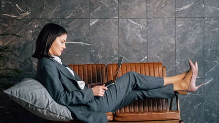 Young woman freelancer sits on brown bench with grey cushion and types on new laptop against marble wall at office reception