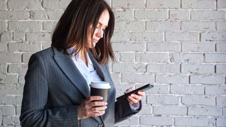 Smiling businesswoman with short dark hair types on black smartphone holding paper coffee cup standing near white brick wall in morning copy space