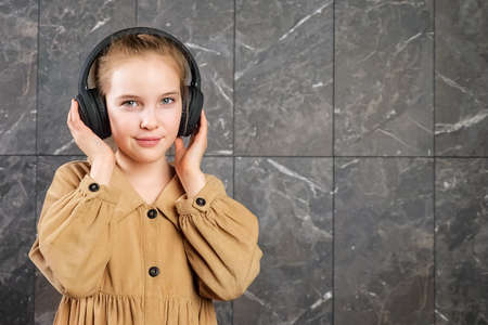 Young lady in brown clothes and black headphones listens to music and dances standing against decorative wall at school during break copy space