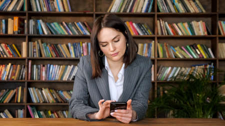 Stylish businesswoman in grey jacket over white blouse types on black smartphone and smiles sitting against book racks in library hall