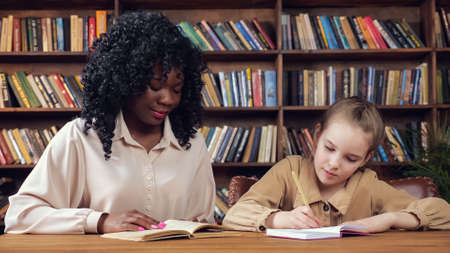 Professional individual Afro-American tutor with long curly hair dictates text to blonde schoolgirl and junior student writes sitting in library Foto de archivo