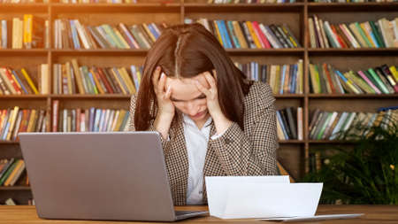 Businesswoman types answer on grey laptop looking at bank letter of account and puts head on hands in despair in office with racks of books Zdjęcie Seryjne