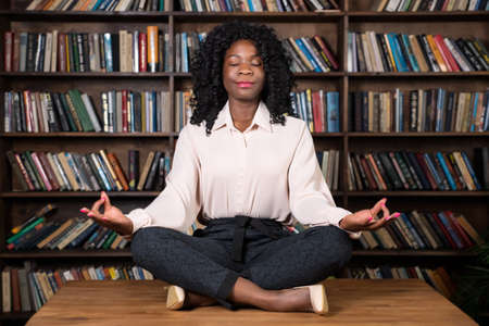 Concentrated Afro-american businesswoman with curly hair meditates sitting in yoga pose lotus on brown wooden table top at office bookshelves