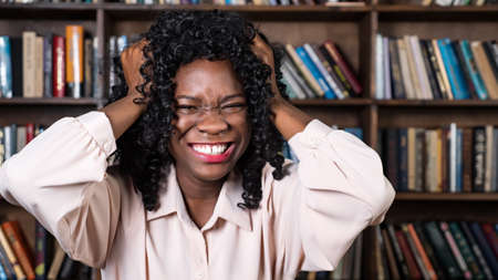 Stressed Afro-american businesswoman with curly hair raises hands to head and screams with despair against wooden racks with books closeup Foto de archivo